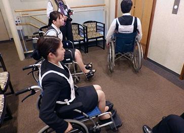 車いすや疑似体験キットを装備して宿泊予定の部屋(UDルーム)に向かう研修のようす